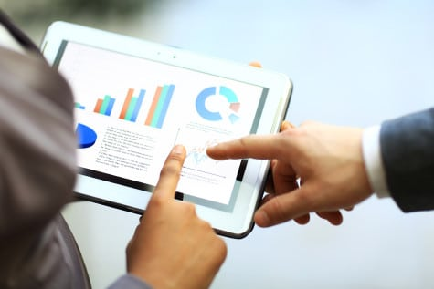 Businessman and woman are looking at a tablet which is showing charts and graphs