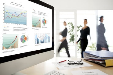 graphs and charts displayed on a MAC screen. Business people are walking in the background