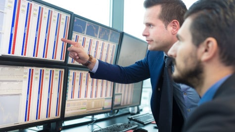 Two traders looking at statistics on their computer screens