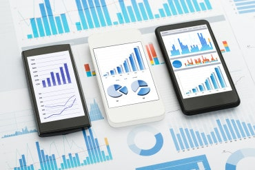 charts and graphs displayed on three smartphones with additional charts showing underneath on paper