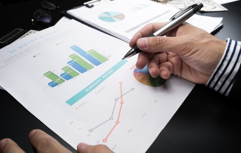 Man analysising business statistical summary report