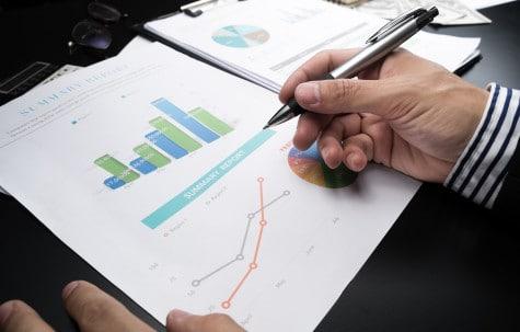 Man analysising business statistical summary report