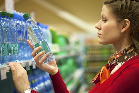 woman looking at a bottle of water while in a supermarket