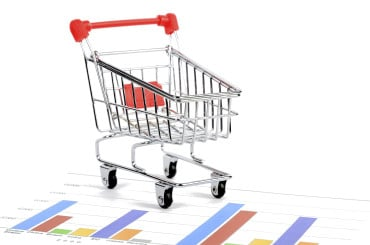 minitature shopping trolley placed on a piece of paper displaying statistical analysis