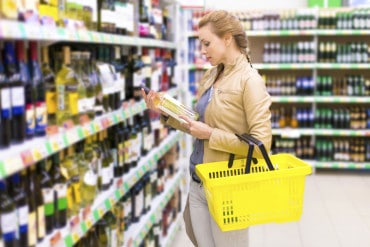 Woman shopping for white wine in a supermarket
